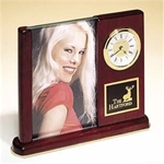 Rosewood piano-finish desk clock features a glass picture frame that will hold a 4 x 6 photograph, as well as a black brass engravable plate.  Supplied with Lifetime Guaranteed Quartz Movement.  Batteries included.  Individually boxed.