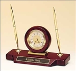 Desk clock with double pen set on a rosewood piano-finish base.  Black brass engravable plate included.  Features a diamond-spun dial and three hand movement.  Supplied with Lifetime Guaranteed Quartz Movement.  Batteries included.  Individually boxed.
