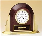 Rosewood piano-finish arched Art Deco style table clock with goldtone metal base.  Includes a black brass engravable plate.  Supplied with Lifetime Guaranteed Quartz Movement.  Batteries included.  Individually boxed.