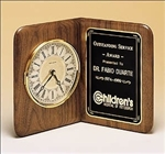 Round quartz clock on free-standing walnut Airflyte edge and decorative black brass engravable plate.  Features a solid brass diamond-spun bezel with glass lens and ivory dial.  Supplied with Lifetime Guaranteed Quartz Movement.  Individually boxed.